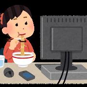 パソコンの前で食事をする女性