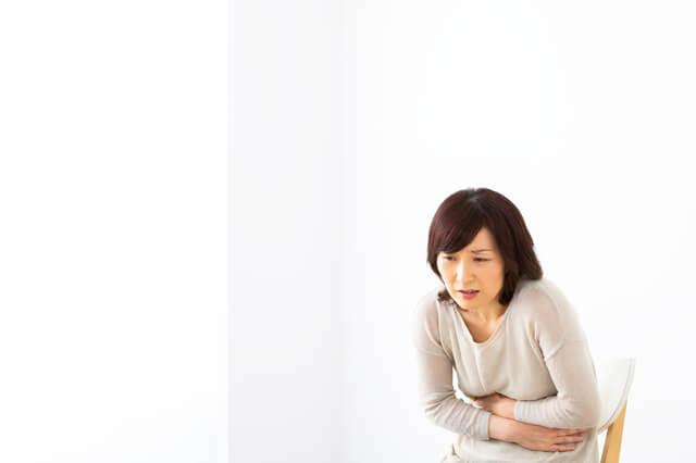 胃の痛みを感じる女性
