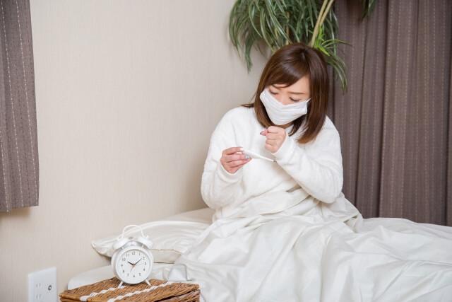 風邪で体温を測る女性